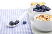Fresh blueberry in white porcelain spoon with bowl of cornflakes, on serviette — Stock Photo