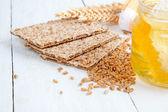 Мёд с деревянной ложкой и хлебцы на деревянных фоне — Стоковое фото