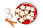 Star shaped cinnamon biscuit on red plate, on white background — Stock Photo