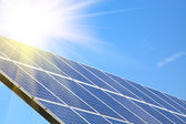 Solar panel against blue sky with sun — Stock Photo