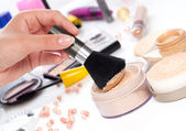 Powder with cosmetic brush, on table wit makeup — Stock Photo