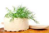 Goat cheese, wooden plate — Stock Photo