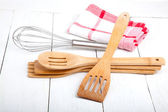Wooden kitchen set with tea towel, on wooden white background. — Stock Photo