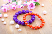 Multi color coral bangles and artificial pearls, with pink flowe — Stock Photo