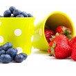 Assorted fresh picked berries in a green mug over a white backgr — Stock Photo