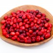 Fresh red berries in wooden bowl, isolated on a white background - Photo