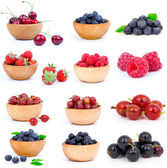 Set of fresh strawberry, Blueberries, Raspberries, cherry, gooseberries and blackcurrants in a wooden bowl, over a white background. — Stok fotoğraf