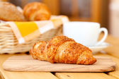 Fresh croissant and white cup coffee, on a wooden table — Stock Photo