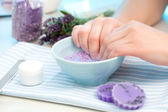 Client soaks her hands in a bowl of fragrant water before manicu — Stock Photo