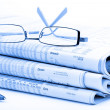Stock Photo: Stack of newspapers and glasses blue toned