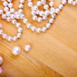 Artificial pearls and pink flower on wooden background — Stock Photo