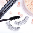 Постер, плакат: Black false eyelashes with mascara and powder on white backgrou