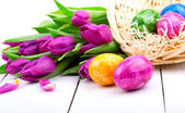 Easter eggs and bouquet tulips, on white wooden — Stock Photo