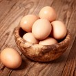 Fresh brown eggs on wooden background — Stock Photo
