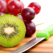 Single cross section of kiwi on grapes background, over whit — Stock Photo #22842810