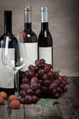 Red grapes with wine bottles on wooden background — Stock Photo