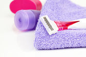 Closeup of pink shaving blade on towel with moisturize — Stock Photo