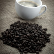 Stock Photo: Black coffee bean with coffee cup, over old burlap background