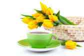 Tea cup with bouquet of fresh yellow tulips on white background — Stok fotoğraf