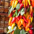 Bunch of multicolored hot peppers with a bay leaf on a market - Stock Photo