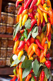 Bunch of multicolored hot peppers with a bay leaf on a market — Stock Photo
