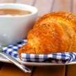 Croissant with marmalade and caffee cup. on wooden backgroun — Stock Photo #27776043
