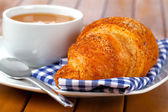 Croissant with marmalade and caffee cup. on wooden backgroun — Stock Photo