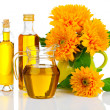 Oil in glass bottle and jug with sunflowers, isolated on white — Stock Photo