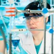 Scientific researcher holding at a liquid solution in a lab — Stock Photo #29997703