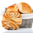 Baked bread bun in basket. isolated on white — Stock Photo