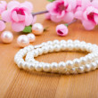 Pearl bangles, with pink flower on wooden background — Stok fotoğraf