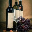 Bottle of vine with wine glass and grapes, on wooden background — Stock Photo