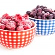 Frozen raspberries and bilberries in the bowl, on a white backgr — Stock Photo