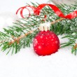Christmas balls and fir branches on a snow background. — Stock Photo