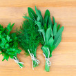 Fresh herbs: parsley dill and sage, over wooden background — Stock Photo #33175125