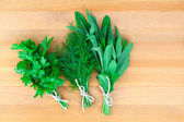 Fresh herbs: parsley dill and sage, over wooden background — Stock Photo