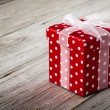 Red gift box with bow on wood background — Stock Photo
