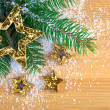 Golden Christmas stars with pine branch and snow on wooden backg — Stock Photo