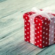 Red gift box with bow on wood background — Stock Photo #35231081