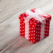 Red gift box with bow on wood background — Stock Photo #35239149