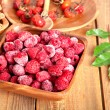 Frozen raspberries in the wooden bowl with spoon — Stok fotoğraf