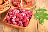 Frozen raspberries in the wooden bowl with spoon — Stock Photo