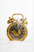 Antique gold clock in the snow. with copy space on a white backg — Stockfoto