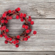 Christmas wreath from red berries on wooden background — Stock Photo