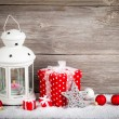 Stock Photo: Burning lantern in snow with christmas decoration, on wood b