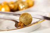 Silver cutlery decorated with a golden Christmas bauble — Stock fotografie