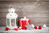 Burning lantern in the snow with christmas decoration, on wood b — Stok fotoğraf