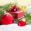 Red Christmas ball with pine branch, gift and snow, on white sno — Stockfoto