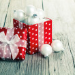 Stock Photo: Red gift box, polkdots with christmas decoration, on wood back