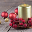 Christmas wreath from red berries with a candle on wooden backgr — Stock Photo